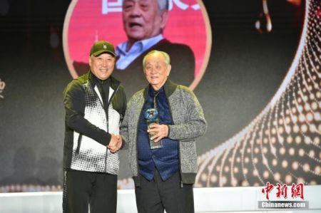 图为李永波为王文教献上奖杯。中新社记者 翟璐 摄
