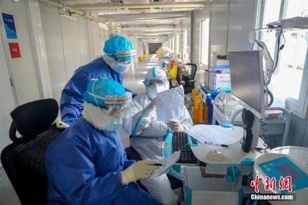 资料图:火神山医院感染二科一病区主任董宇超(白衣者)与同事一起查对患者信息。中新社记者 张畅 摄