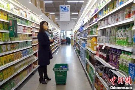 """(当地时间2月10日,微信群""""多伦多爱心互助隔离同胞群""""的""""群主""""孙女士在大多伦多地区万锦市一家华人超市为一位正在自我隔离的孕妇采购食物和生活用品。 中新社记者 余瑞冬 摄)"""
