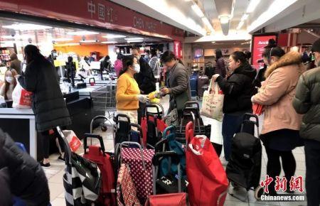 """资料图:在""""封城""""前夜,大批民众在巴黎的超市排队抢购生活必需品。中新社记者 李洋 摄"""