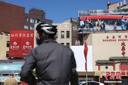 """当地时间5月12日,纽约曼哈顿唐人街,一个广告牌上写着""""纽约勇往直前""""。中新社记者 廖攀 摄"""