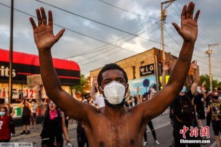 """大批当地民众走上街头,要求为死者""""伸张正义"""",示威者向警察投掷瓶子和石块,警方则出动催泪弹、爆震弹、闪光弹和橡皮子弹等武器驱赶示威者,进一步激化矛盾。图为一名抗议者带着口罩进行示威。"""