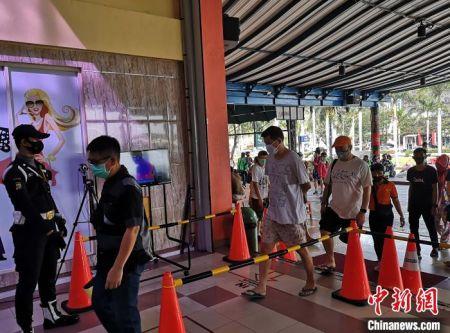 图为进入市场的顾客排队接受红外线体温检测。 林永传 摄