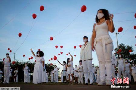 资料图:当地时间6月1日,巴西首都巴西利亚,艺术家们手持红色气球悼念在新冠疫情中不幸离世的人们。