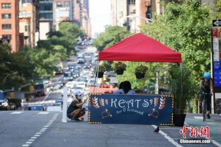 当地时间7月16日,美国纽约曼哈顿,一家餐厅的工作人员在布置户外就餐区。因防疫需要,纽约市原本应在第三阶段开放的餐饮业室内就餐仍处于暂停状态,政府鼓励餐厅申请设置户外就餐区。中新社记者 廖攀 摄