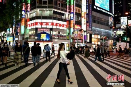资料图:5月25日,日本解除紧急事态宣言,人们穿过东京新宿区的一条街道。