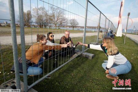 资料图:德国瑞士封锁边界,两国民众隔护栏聚餐 。