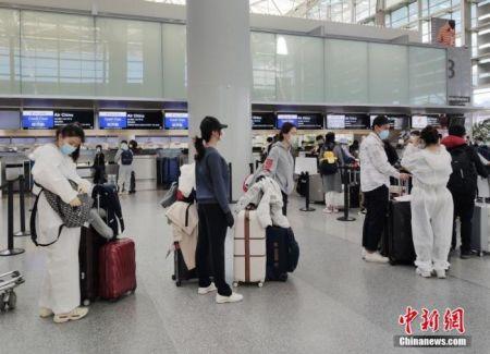 资料图:前往中国的乘客采取严密防护措施,在美国旧金山国际机场排队办理登机手续。中新社记者 刘关关 摄